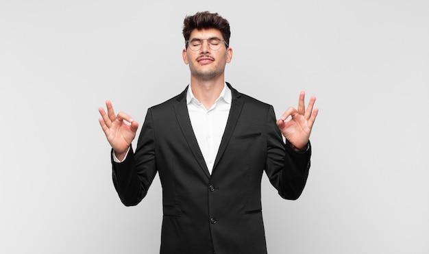 Jonge knappe man die geconcentreerd kijkt en mediteert, zich tevreden en ontspannen voelt, denkt of een keuze maakt