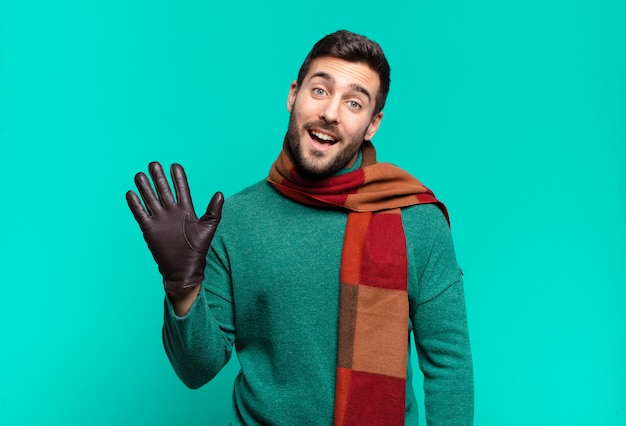 Jonge knappe man die gelukkig en opgewekt lacht, met de hand zwaait, je verwelkomt en begroet, of afscheid neemt. koud en winterconcept