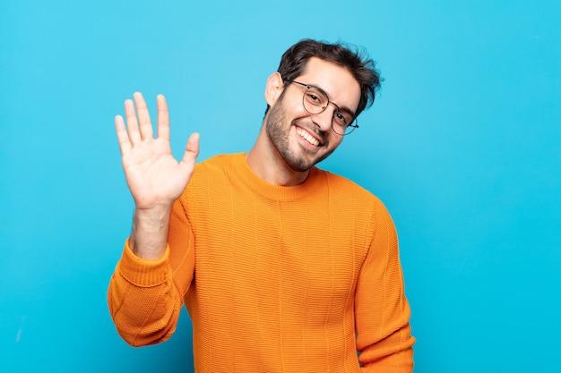 Jonge knappe man die gelukkig en opgewekt lacht, met de hand zwaait, je verwelkomt en begroet, of afscheid neemt