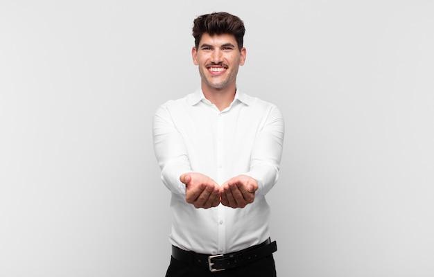 Jonge knappe man die gelukkig glimlacht met een vriendelijke, zelfverzekerde, positieve blik, een object of concept aanbiedt en toont