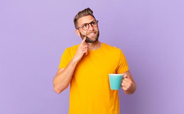 Jonge knappe man die gelukkig lacht en dagdroomt of twijfelt. en een koffiemok vasthouden