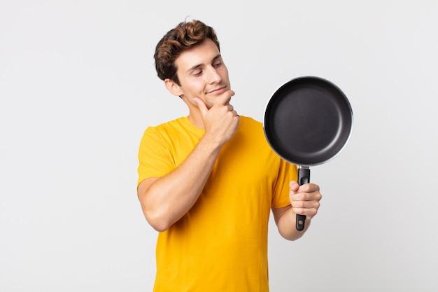 Jonge knappe man die gelukkig lacht en dagdroomt of twijfelt en een kookpan vasthoudt