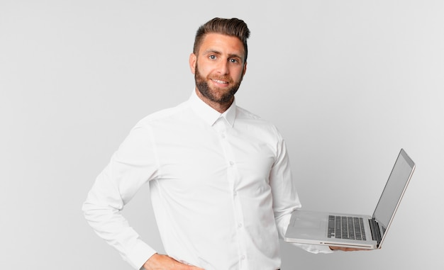 Jonge knappe man die gelukkig lacht met een hand op de heup en zelfverzekerd en een laptop vasthoudt