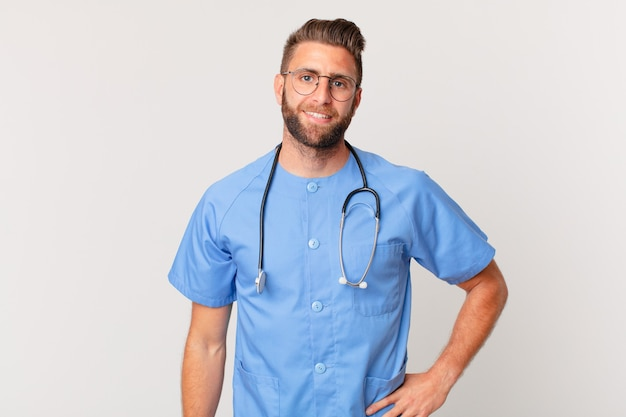 Jonge knappe man die gelukkig lacht met een hand op de heup en zelfverzekerd. verpleegster concept
