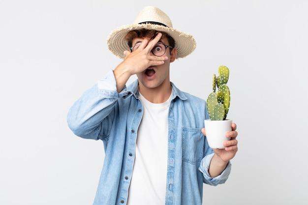Jonge knappe man die geschokt, bang of doodsbang kijkt en zijn gezicht bedekt met de hand. boer met een decoratieve cactus