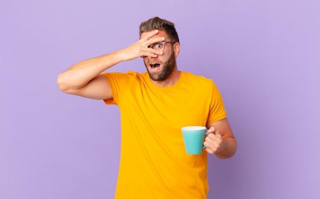 Jonge knappe man die geschokt, bang of doodsbang kijkt en zijn gezicht bedekt met de hand. en een koffiemok vasthouden