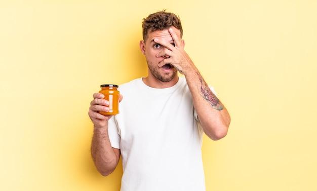 Jonge knappe man die geschokt, bang of doodsbang kijkt en zijn gezicht bedekt met de hand. perzik gelei concept