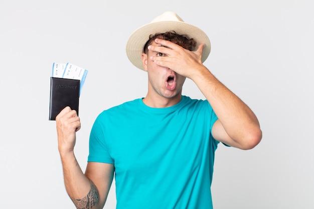 Jonge knappe man die geschokt, bang of doodsbang kijkt en zijn gezicht bedekt met de hand. reiziger met zijn paspoort