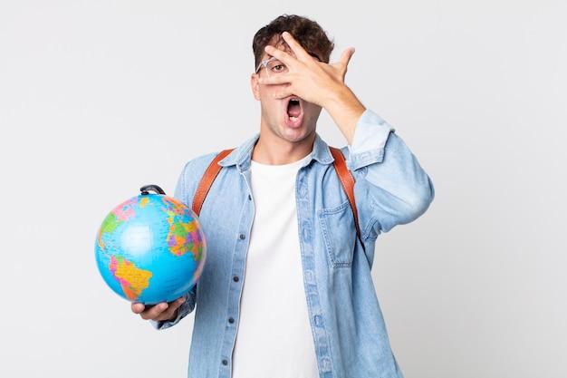 Jonge knappe man die geschokt, bang of doodsbang kijkt en zijn gezicht bedekt met de hand. student met een wereldbolkaart