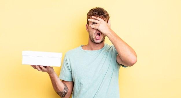 Jonge knappe man die geschokt, bang of doodsbang kijkt en zijn gezicht bedekt met de hand. witte doos concept