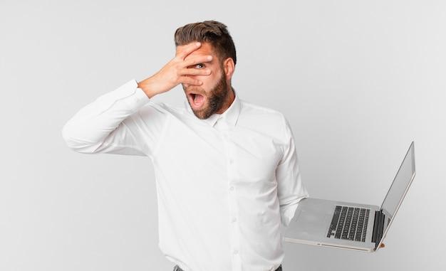 Jonge knappe man die geschokt, bang of doodsbang kijkt, zijn gezicht bedekt met de hand en een laptop vasthoudt