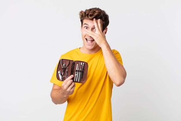 Jonge knappe man die geschokt, bang of doodsbang kijkt, zijn gezicht bedekt met de hand en een nagelkoffer vasthoudt