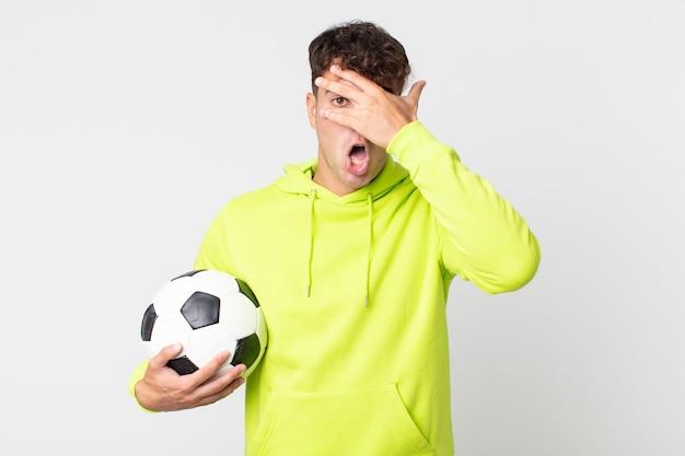 Jonge knappe man die geschokt, bang of doodsbang kijkt, zijn gezicht bedekt met de hand en een voetbal vasthoudt