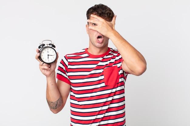 Jonge knappe man die geschokt, bang of doodsbang kijkt, zijn gezicht bedekt met de hand en een wekker vasthoudt