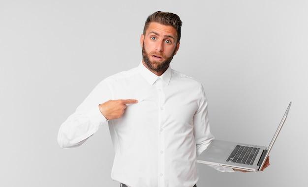 Jonge knappe man die geschokt en verrast kijkt met de mond wijd open, naar zichzelf wijst en een laptop vasthoudt
