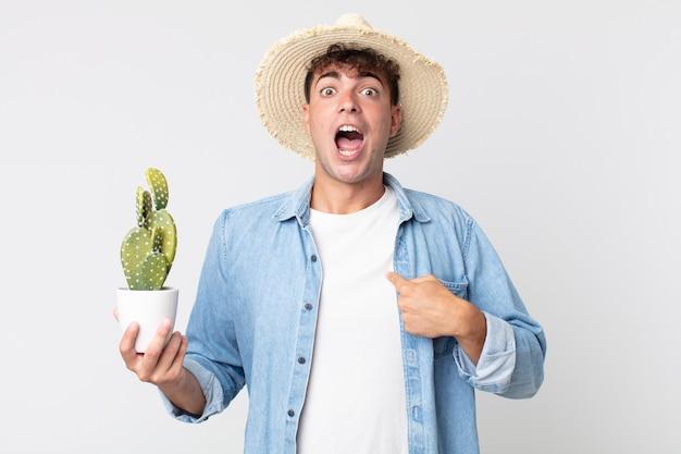 Jonge knappe man die geschokt en verrast kijkt met wijd open mond, wijzend naar zichzelf. boer met een decoratieve cactus