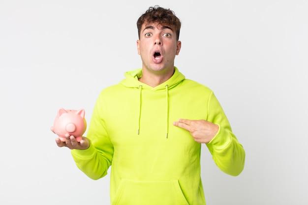Jonge knappe man die geschokt en verrast kijkt met wijd open mond, wijzend naar zichzelf en een spaarvarken vasthoudend