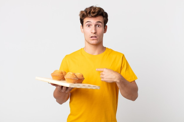 Jonge knappe man die geschokt en verrast kijkt met wijd open mond, wijzend naar zichzelf met een dienblad met muffins