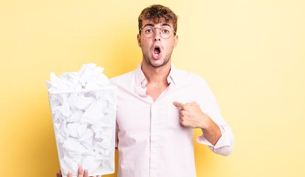 Jonge knappe man die geschokt en verrast kijkt met wijd open mond, wijzend naar zichzelf. papier ballen prullenbak concept