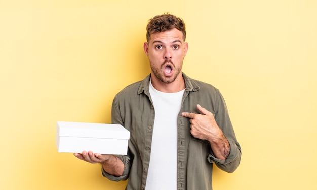 Jonge knappe man die geschokt en verrast kijkt met wijd open mond, wijzend naar zichzelf. witte doos concept