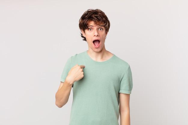 Jonge knappe man die geschokt en verrast kijkt met wijd open mond, wijzend naar zichzelf
