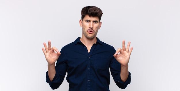 Jonge knappe man die geschokt, verbaasd en verrast is, goedkeuring toont en goed teken met beide handen maakt
