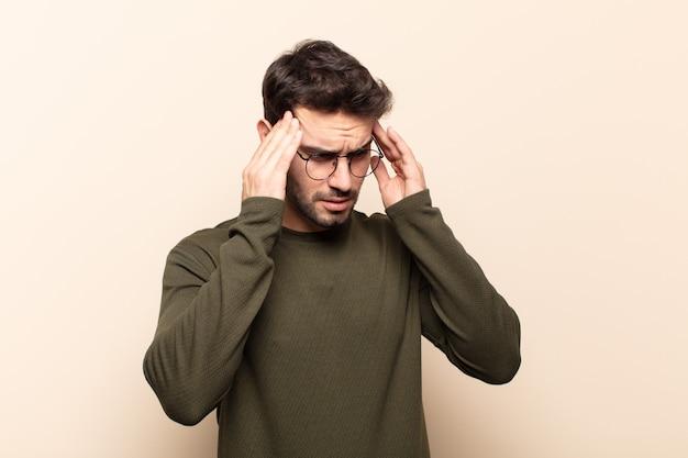 Jonge knappe man die gestrest en gefrustreerd kijkt, onder druk werkt met hoofdpijn en last heeft van problemen