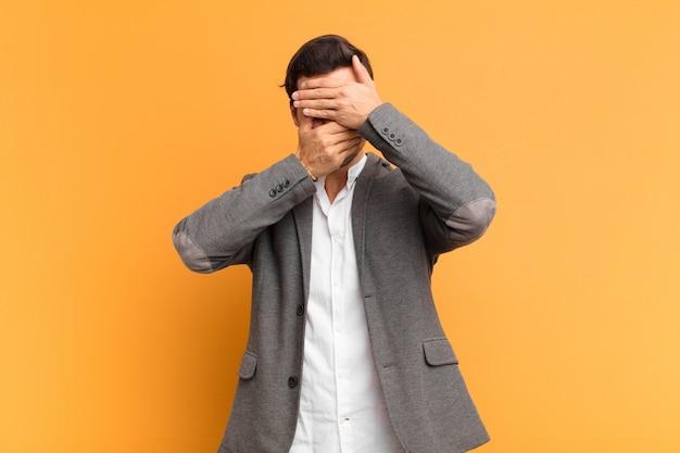 Jonge knappe man die gezicht bedekken met beide handen nee zeggen! afbeeldingen weigeren of foto's verbieden