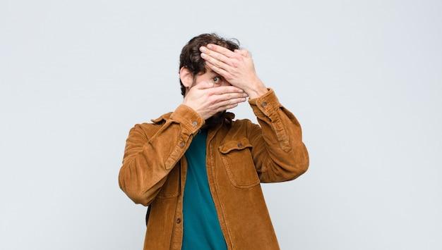 Jonge knappe man die gezicht bedekt met beide handen nee zeggen tegen de camera! afbeeldingen weigeren of foto's over de muur verbieden