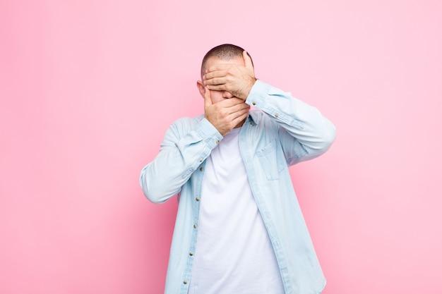 Jonge knappe man die gezicht bedekt met beide handen nee zeggen tegen de camera! afbeeldingen weigeren of foto's tegen de muur verbieden