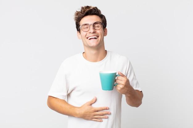 Jonge knappe man die hardop lacht om een hilarische grap en een koffiekopje vasthoudt
