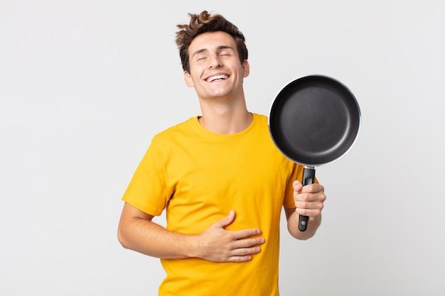 Jonge knappe man die hardop lacht om een hilarische grap en een kookpan vasthoudt