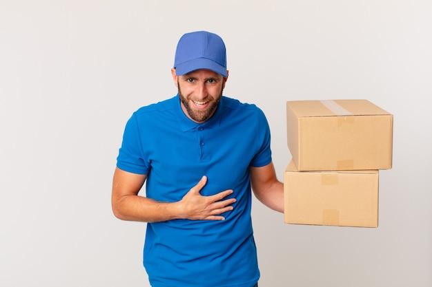 Jonge knappe man die hardop lacht om een hilarische grap. pakket leveren concept