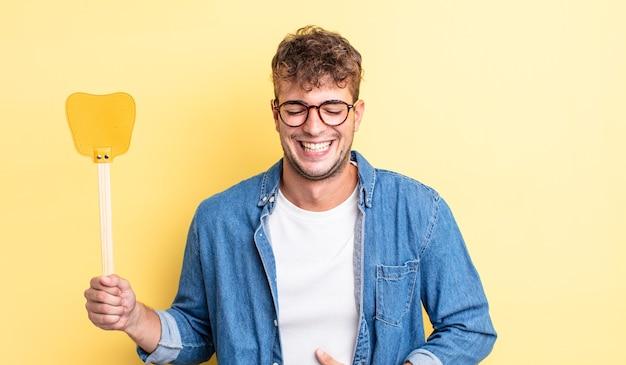 Jonge knappe man die hardop lacht om een hilarische grap. vliegenmepper concept