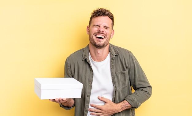 Jonge knappe man die hardop lacht om een hilarische grap. witte doos concept