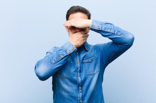 Jonge knappe man die het gezicht bedekt met beide handen en nee zegt tegen de camera! afbeeldingen weigeren of foto's verbieden