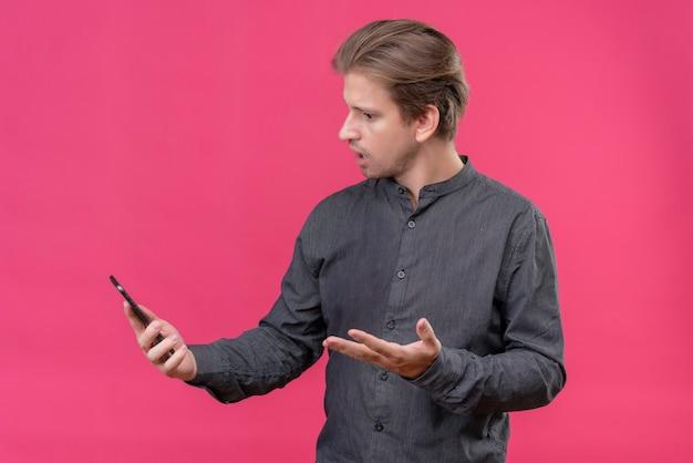 Jonge knappe man die het scherm van zijn mobiele telefoon bekijkt