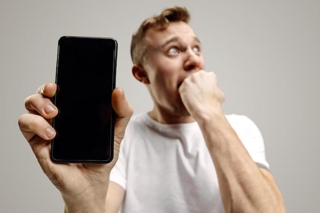 Jonge knappe man die het smartphonescherm over grijs met een verrassingsgezicht toont.