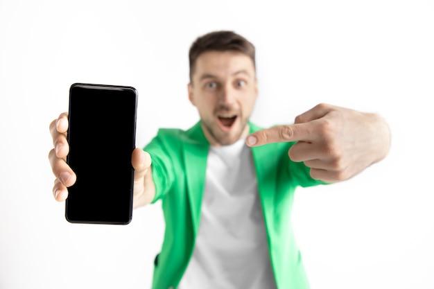 Jonge knappe man die het smartphonescherm toont en ok ondertekent die op grijze muur wordt geïsoleerd
