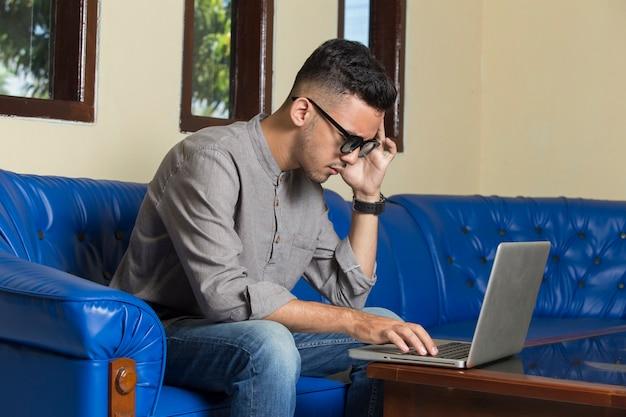 Jonge knappe man die hoofdpijn heeft terwijl hij thuis op de bank zit en online op een laptop werkt