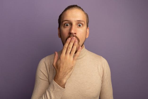 Jonge knappe man die in beige coltrui voorzijde bekijkt die geschokt wordt die mond bedekt met hand die zich over lila muur bevindt