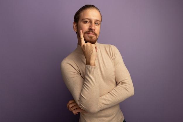 Jonge knappe man die in beige coltrui voorzijde met hand op zijn kin bekijkt denken die zich over lila muur bevindt