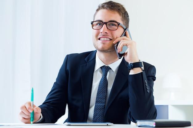 Jonge knappe man die in zijn kantoor met mobiele telefoon werkt.