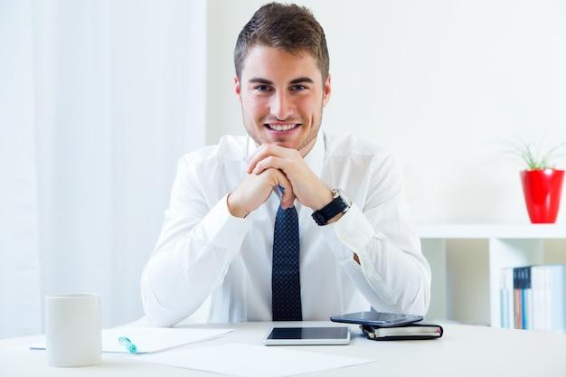 Jonge knappe man die in zijn kantoor werkt.