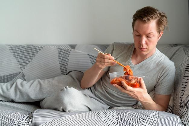 Jonge knappe man die kimchi eet terwijl hij thuis op de bank ligt