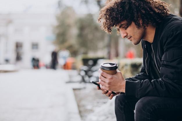Jonge knappe man die koffie drinkt en op straat loopt