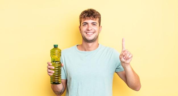 Jonge knappe man die lacht en er vriendelijk uitziet, met nummer één. olijfolie concept