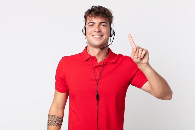 Jonge knappe man die lacht en er vriendelijk uitziet, met nummer één. telemarketeer concept