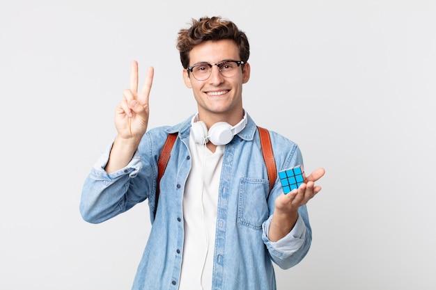 Jonge knappe man die lacht en er vriendelijk uitziet, met nummer twee. intelligentie spelconcept