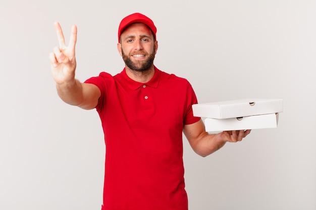 Jonge knappe man die lacht en er vriendelijk uitziet, met nummer twee. pizza bezorgconcept